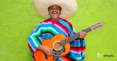 A jolly man with a sombrero and a guitar sings