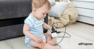 A baby plays with electric cords