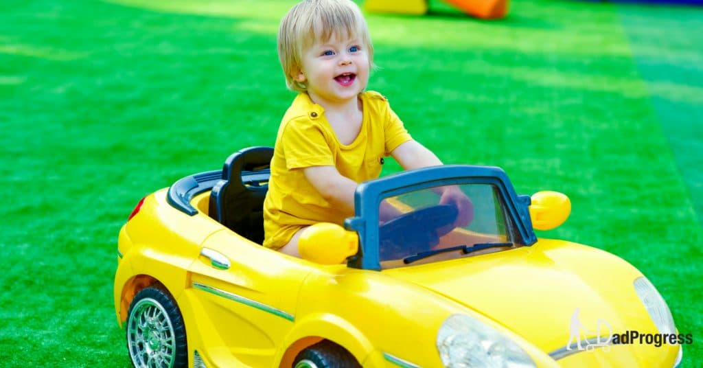 A toddler sitting in a big yellow plastic car