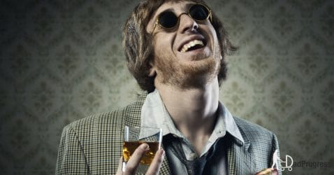 A dude with sunglasses holding a whiskey glass
