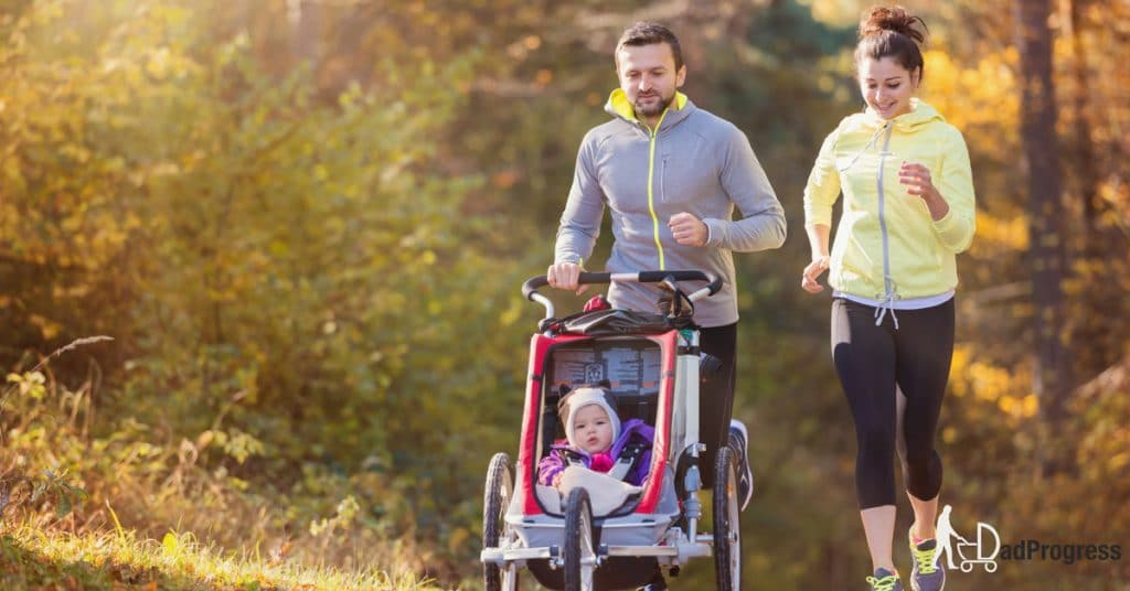 Dad and mom running with a baby in the jogging stroller
