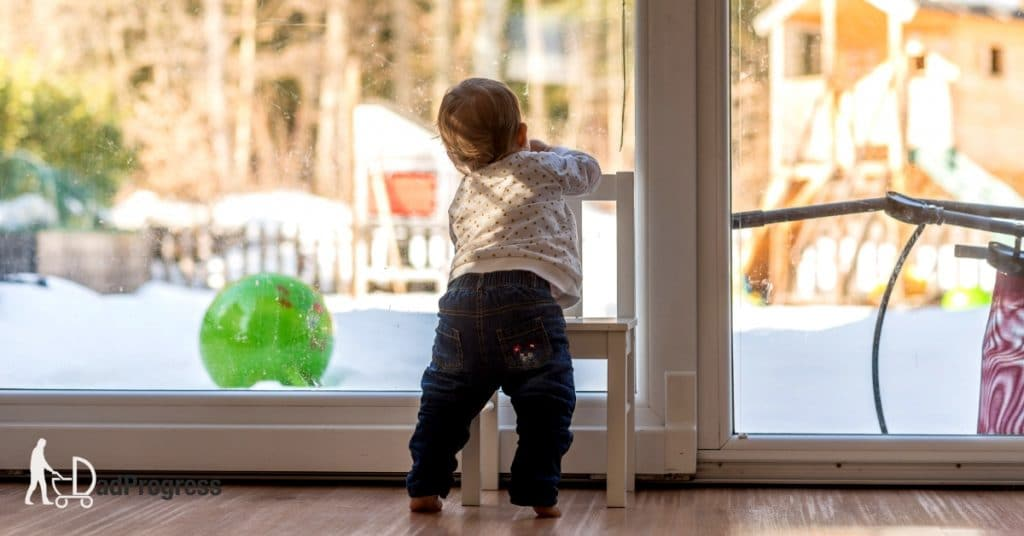 Toddler looking outside where there's snow