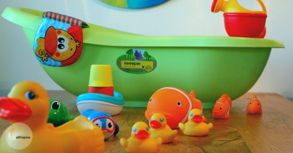 Many Best Bath Toys (e.g, penguin, rubber duck) On A Wooden Table And Tub On The Background