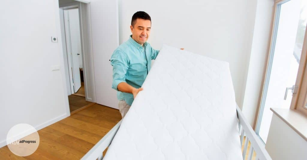 A man moving a mattress to a crib