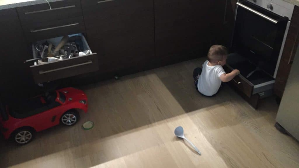 Bored Toddler And A Red Toy Car Behind Him