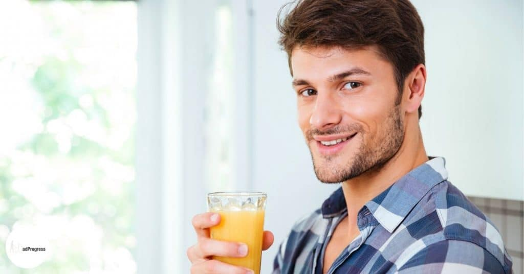 A man drinking orange juice