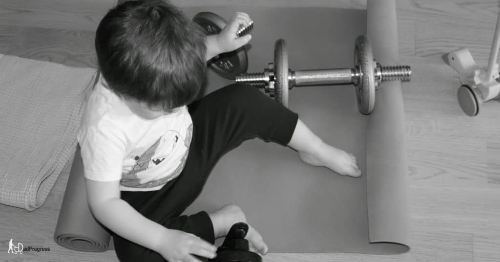 Toddler On a Gym Mat With Dumbbells