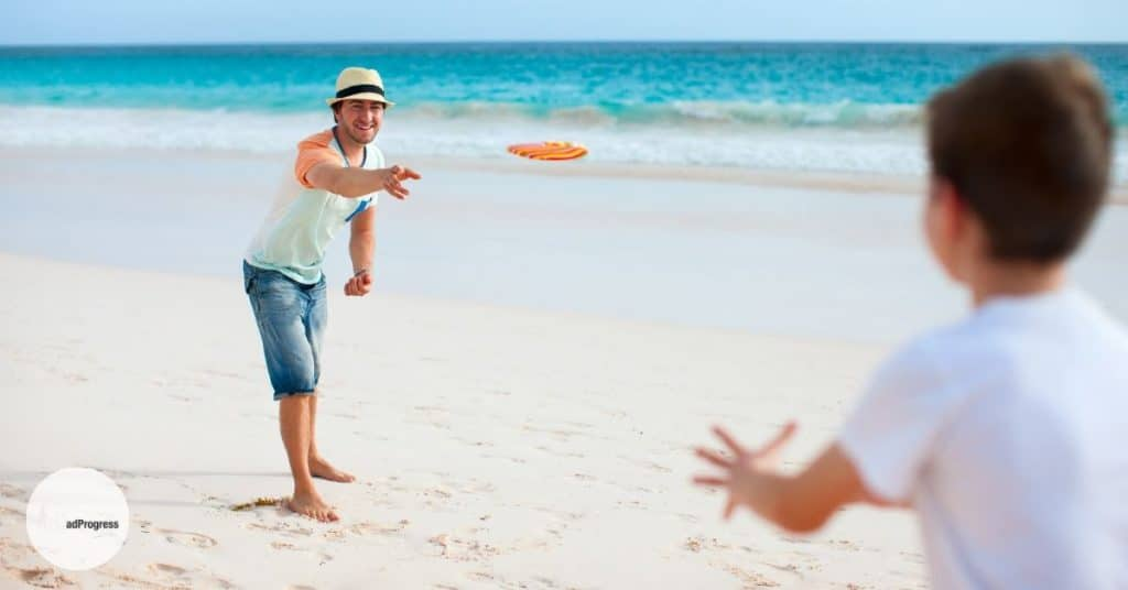 Dad Throws A Flying Disc To His Son On A Beach