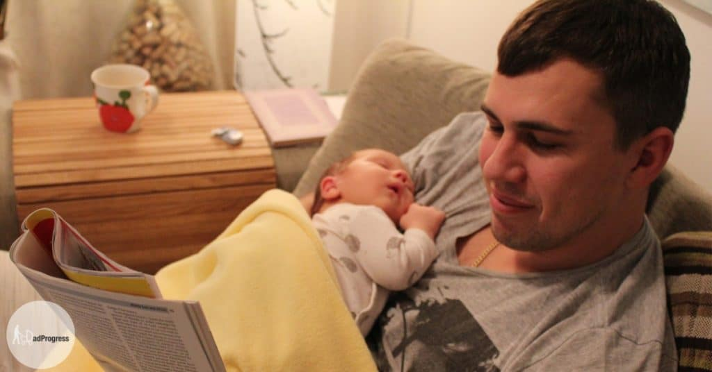 Father holding a baby and reading a paper