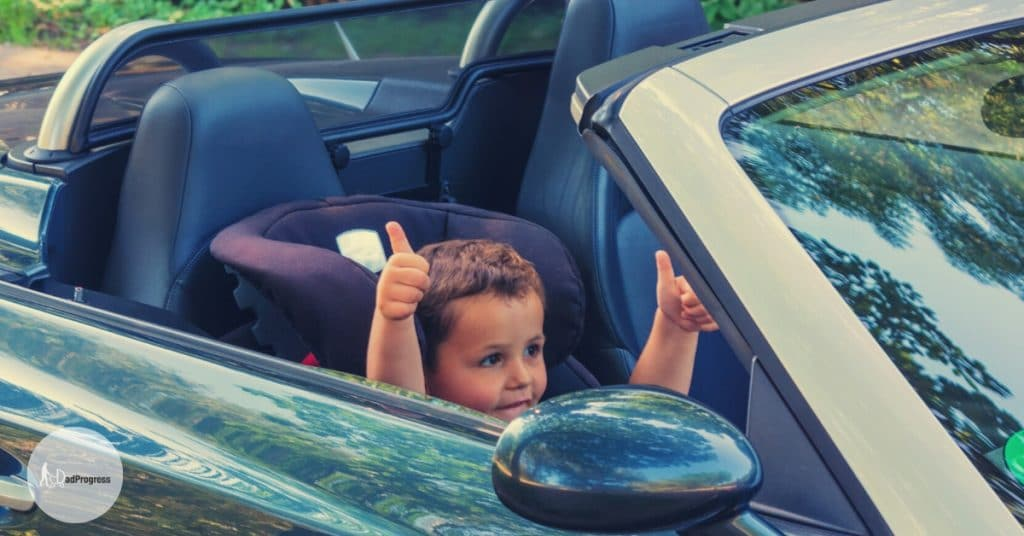 A boy in a car thumbs up