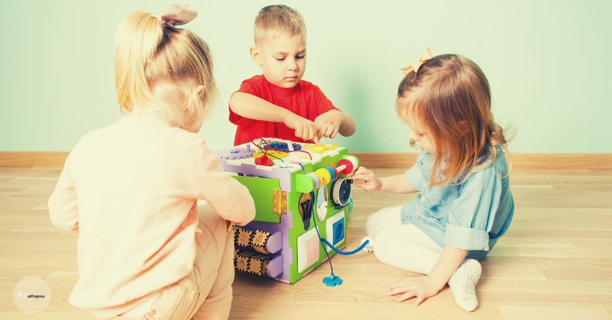 Three toddlers playing with an activity table