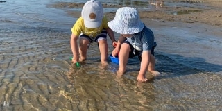 Two toddlers playing in water outside