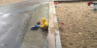 Toddler sitting in a puddle