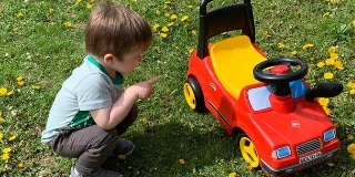Toddler and a roide on toy on grass
