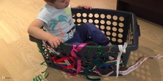 Toddler sitting in a basket that has many ribbons attached to it