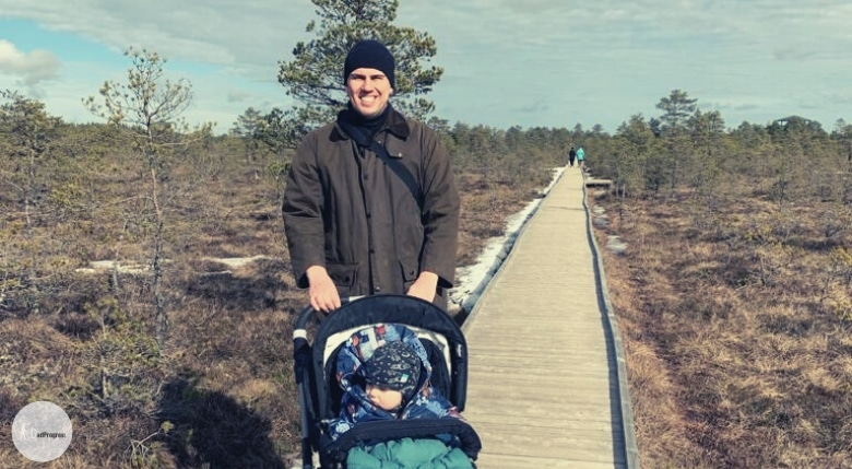 A dad is hiking with a baby (he's in a stroller)