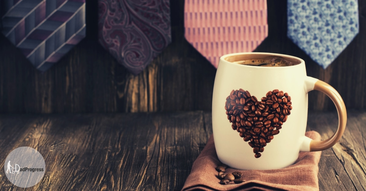 A coffee mug with a heart and ties hanging in the background