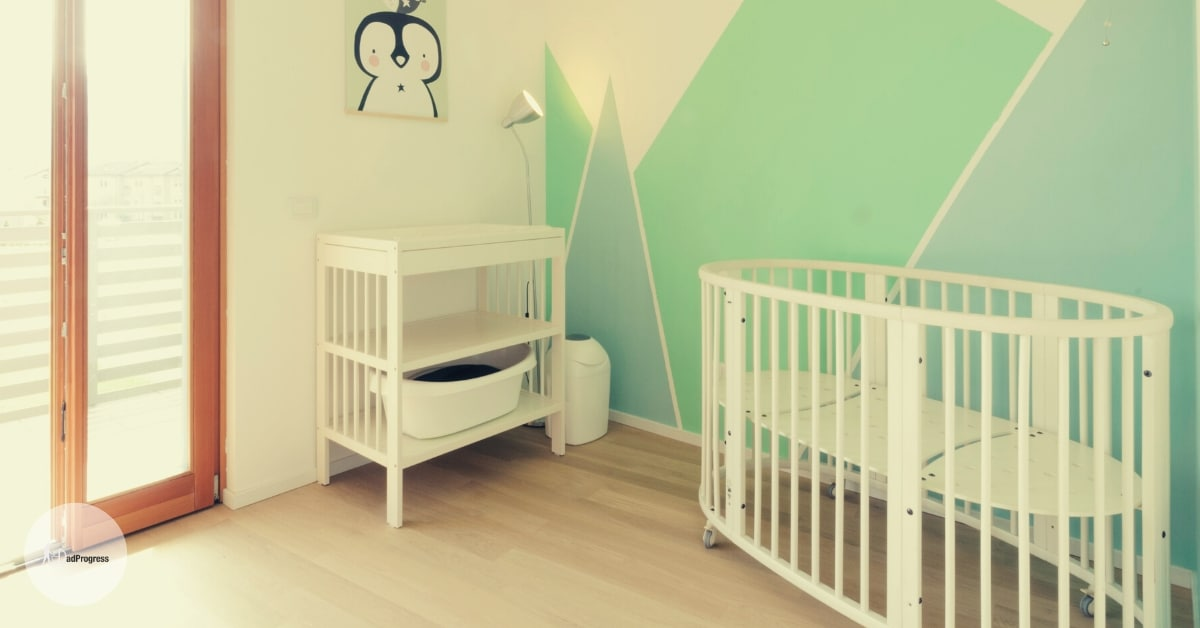A nursery (two main items are a white round mini crib and a changing table)