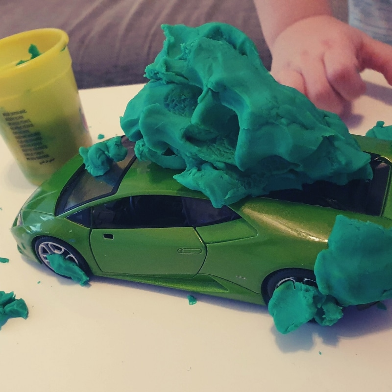 Green toy car covered with green playdough