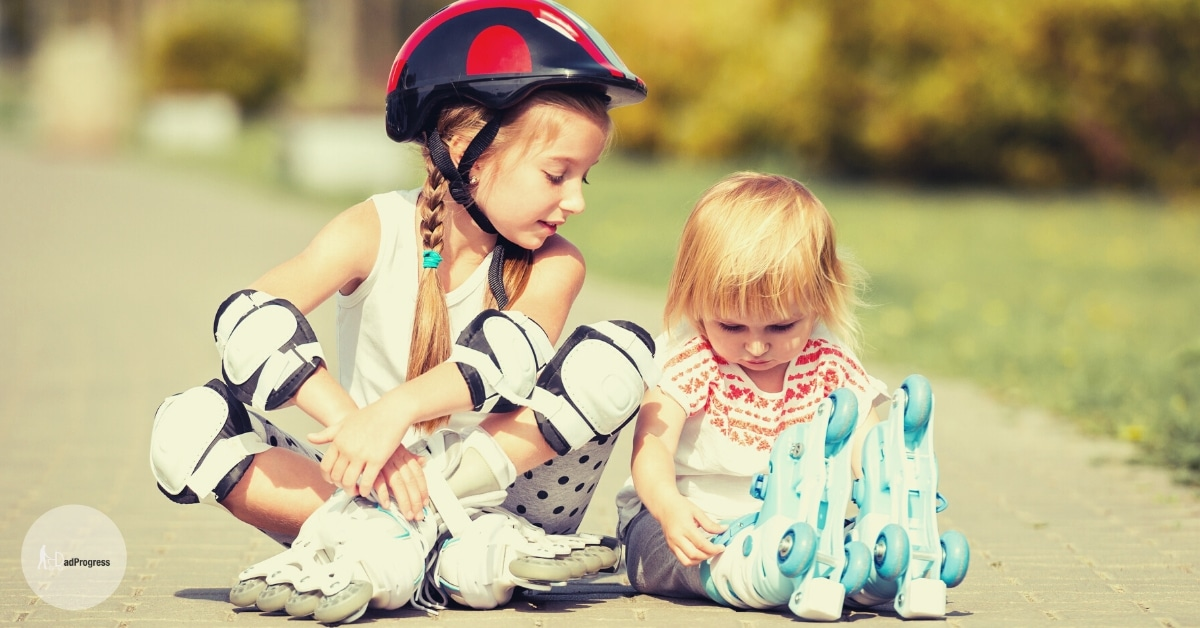 Two Young Girls With Roller Skates Sitting, The Bigger One is Wearing A Helmet