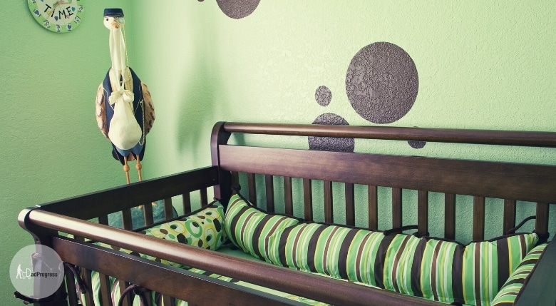 Brown crib with changing table is partly in the picture. Nursery is decorated with green and brown