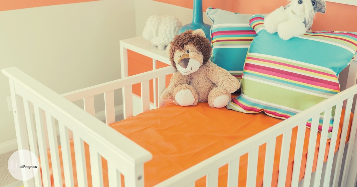 Dream On Me Cribs Reviews featured image shows a white crib that has an orange sheet and two pillows and stuffed animals in it. A small night table with orange doors is in the background