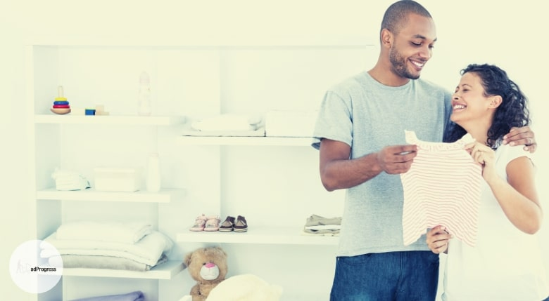 Happy couple looking at a baby shirt and behind them are white shelves with baby items
