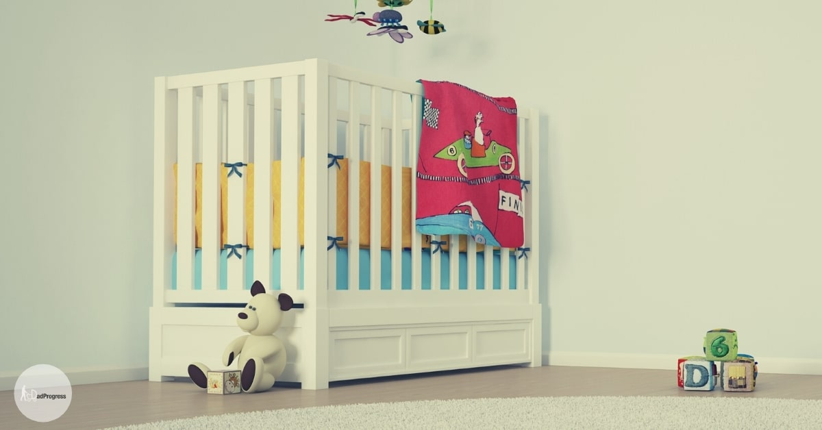 Baby Crib With Drawer Underneath and a couple of toys in an empty nursery