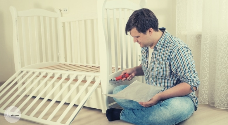 Man assembles a Baby a Crib With Drawers Underneath