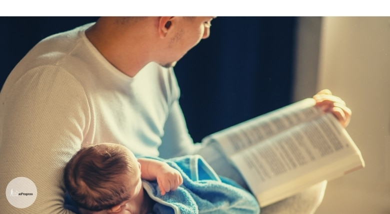 Dad Reading To A Baby From A Glider