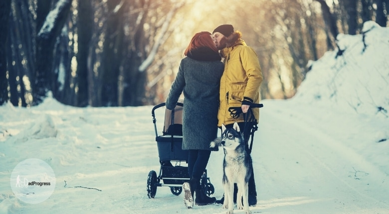 A couple with a stroller and a dog kissing in the winter outside