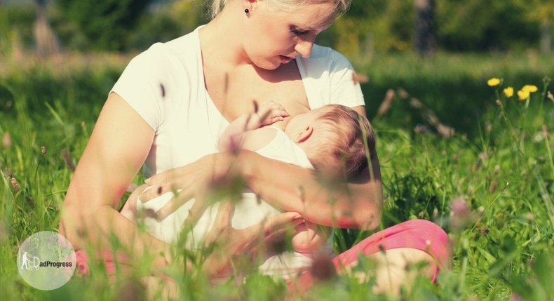 A woman breastfeeding a baby outside on grass