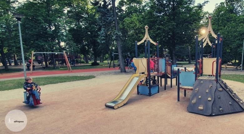 A park with outdoor toys and one toddler in the foreground in the left on a play horse