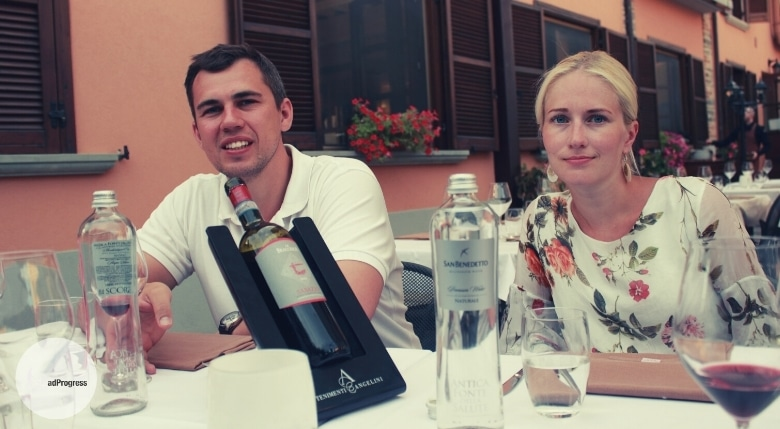 Two people with a glass of wine sitting outside in a restaurant