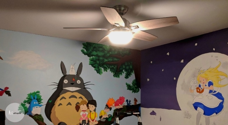 A nursery with a fan and there are cartoon characters painted on the walls (floor is not seen)