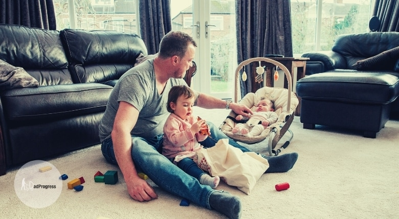 A father with his two children in a room, the baby is in a bouncer