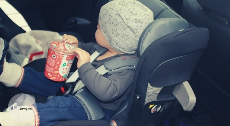 Baby in a car seat in a car looking away