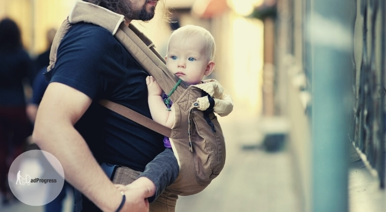 Dad carries a baby in a baby carrier