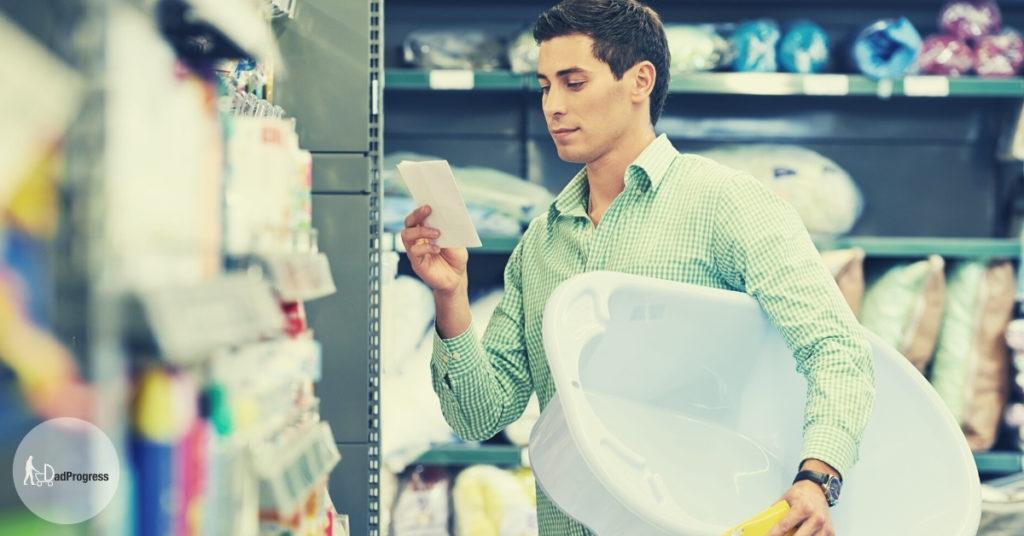 Man holding a baby bathtub and a shopping list