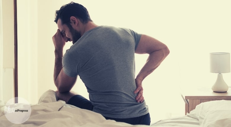 Man with back pain trying to raise up from bed