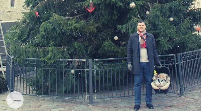 Me with an infant carrier standing in front of a christmas tree