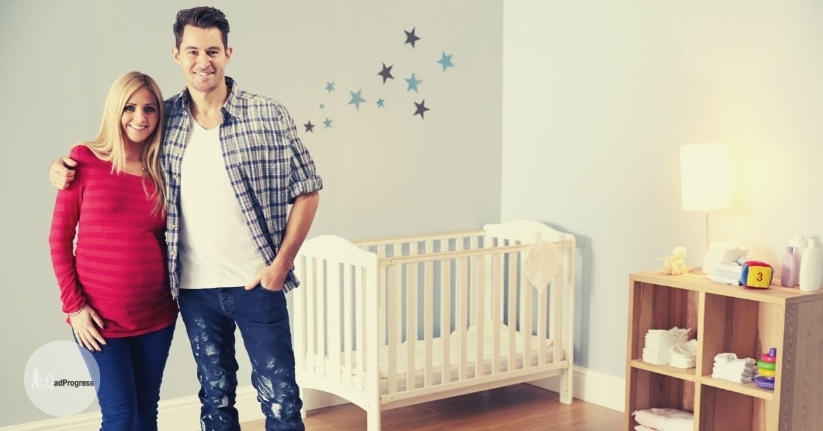 A dad-to-be with a pregnant partner in a nursery preparing for a nursery set up