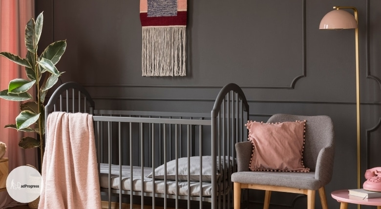 Grey- and pin-themed nursery. A grey chair next to a crib and there's a pink lamp and a small pink table for all the essentials next to it
