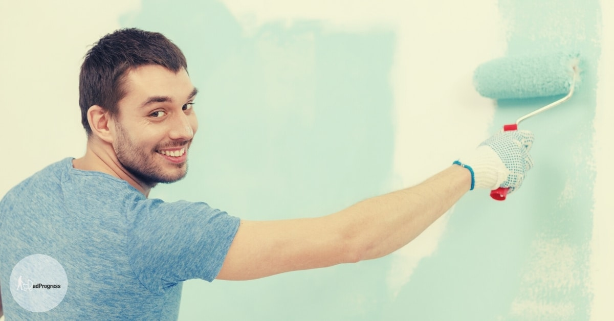 Setting up a nursery featured image- dad painting a wall with blue paint and smiling