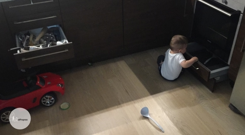 1-year-old sitting on the floor and taking stuff out of drawers in the kitchen