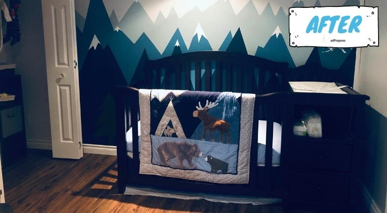 A blue-themed nursery with mountains painted on the wall, baby crib is black and and a baby blanket with wild animals is on the crib