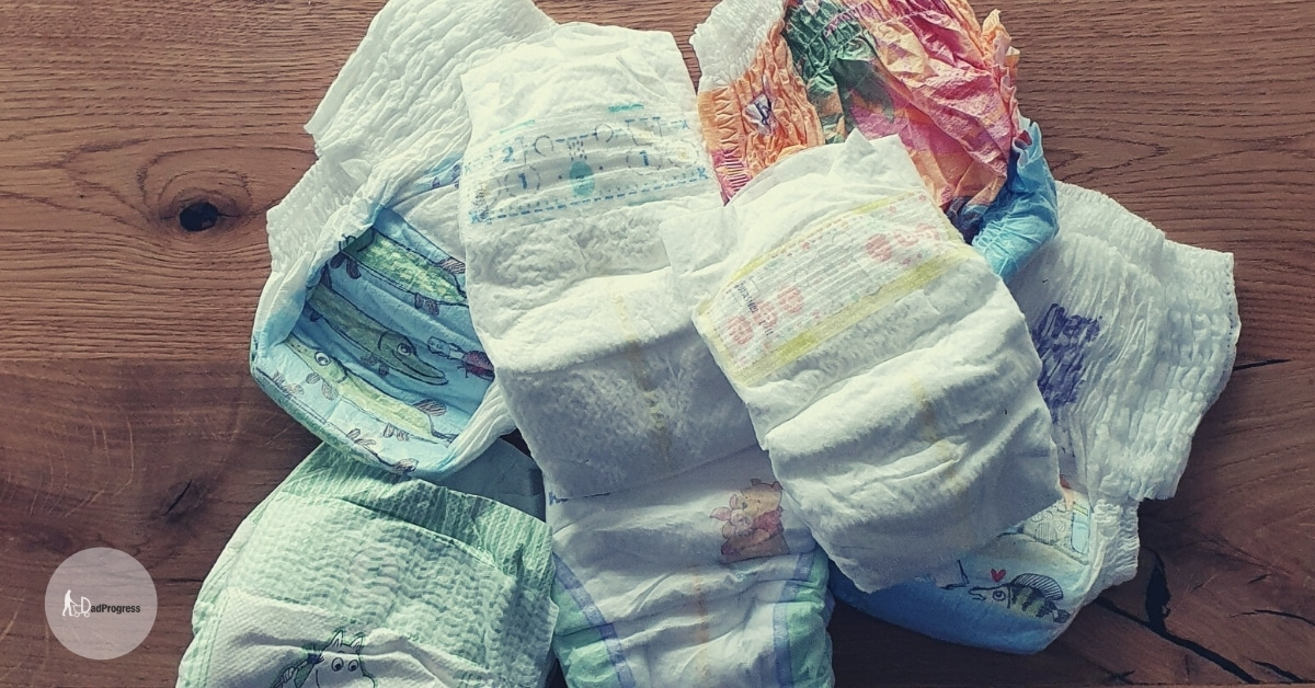 Pile of different unused diapers on a wooden table
